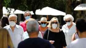 Varias personas caminan por una calle del centro de Córdoba con mascarillas.