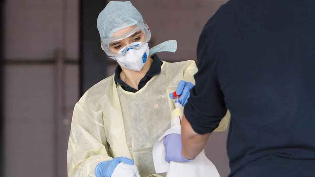 Un sanitario se desinfecta las manos.