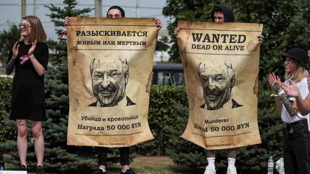 Manifestantes sostienen pancartas de 'busca y captura' contra Lukashenko en Bielorrusia.