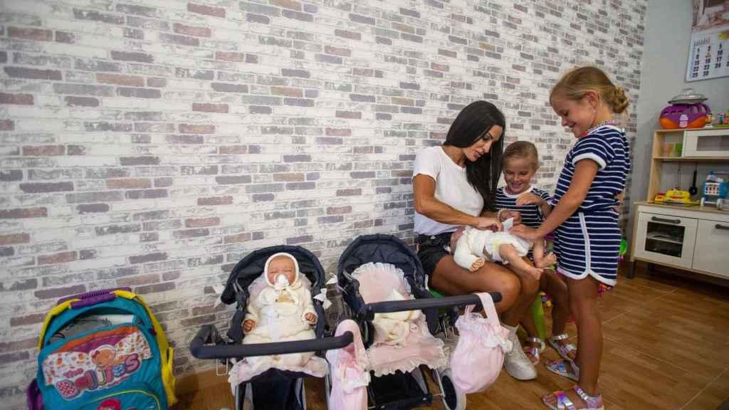 Las gemelas Elisabeth y Julia jugando con unas muñecas junto a su madre.