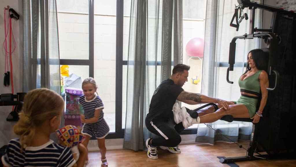 Una dura sesión de entrenamiento mientras sus dos hijas pequeñas juegan junto a las máquinas.