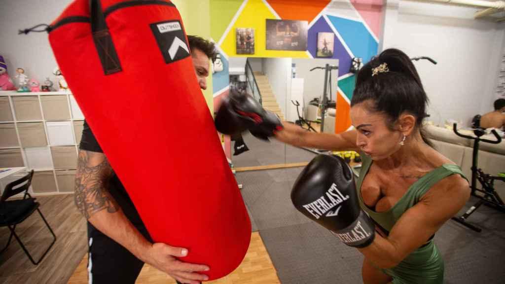 Elisabeth golpeando un saco sostenido por Luis, su entrenador personal.