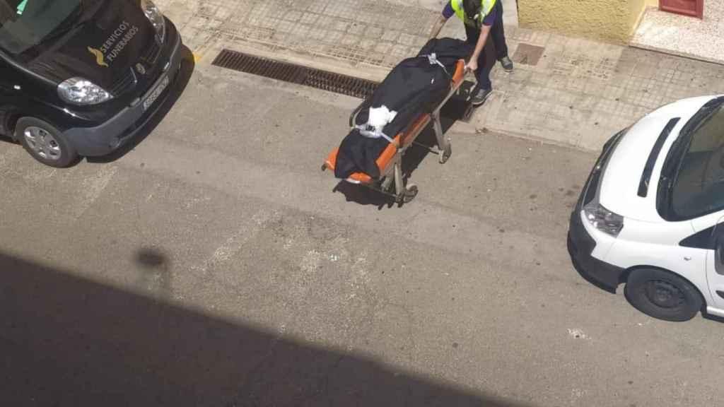 Un empleado de los servicios funerario sacando el cuerpo sin vida de Ana del bloque de pisos.