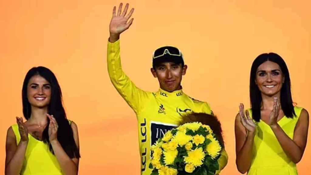 Egan Bernal con el maillot amarillo de la edición de 2019 junto a dos azafatas