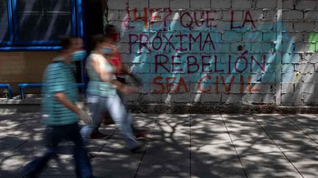 Personas caminando frente a un grafiti en Caracas.