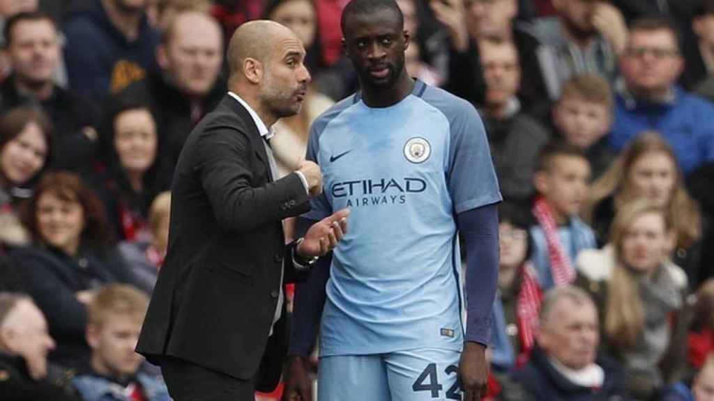 Yaya Touré y Guardiola conversan durante un partido del Manchester City