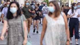Varias personas caminan con mascarillas por el centro de Madrid.