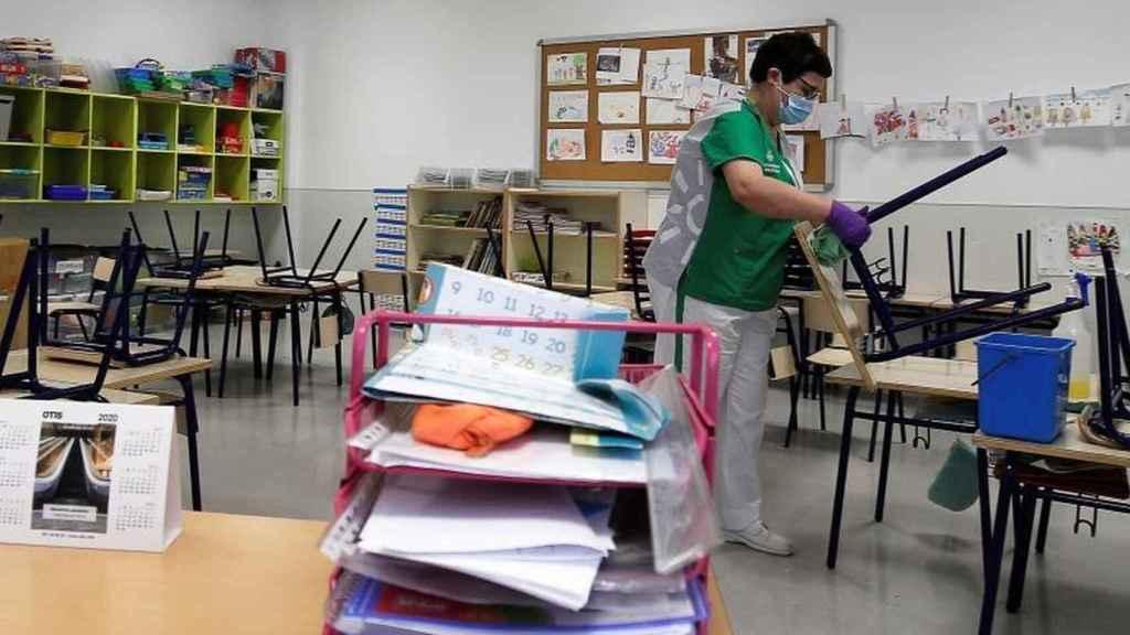 Un trabajadora, desinfectando el aula de una colegio.