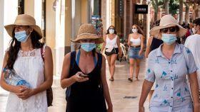 Tres mujeres con mascarilla pasean por Menorca.