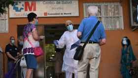 Varias personas esperan su turno para las pruebas aleatorias de PCR en el distrito de Carabanchel, en Madrid.