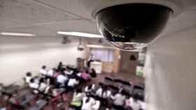 Una cámara graba en un aula, mientras explica el profesor.