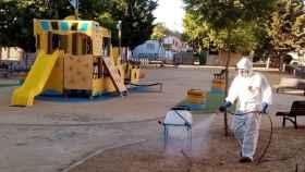 Un operario fumigando un parque infantil.