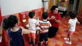 Una profesora explica a un grupo de menores cómo lavarse las manos.