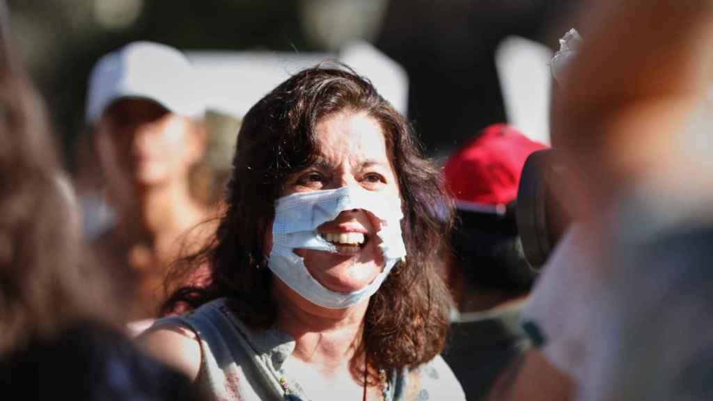 Una mujer, con la mascarilla rota, en el concentración negacionista de la plaza de Colón, Madrid.