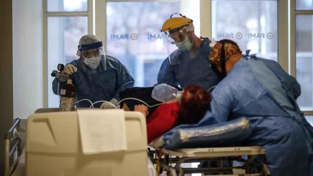 Personal médico traslada en camilla a una paciente COVID-19.