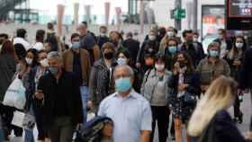 Gente paseando con mascarilla.