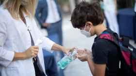 Un niño se desinfecta las manos a la entrada del colegio.