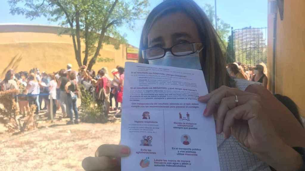 Una profesora muestra el folleto en el que se les pide que eviten aglomeraciones