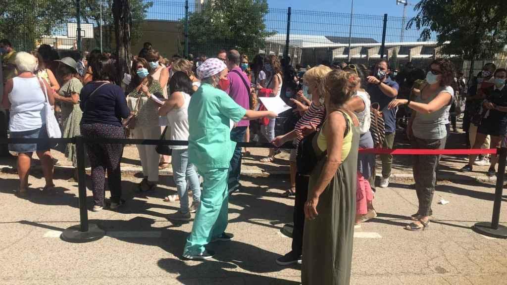 Una enfermera reparte las hojas de consentimiento entre los profesores de la fila.