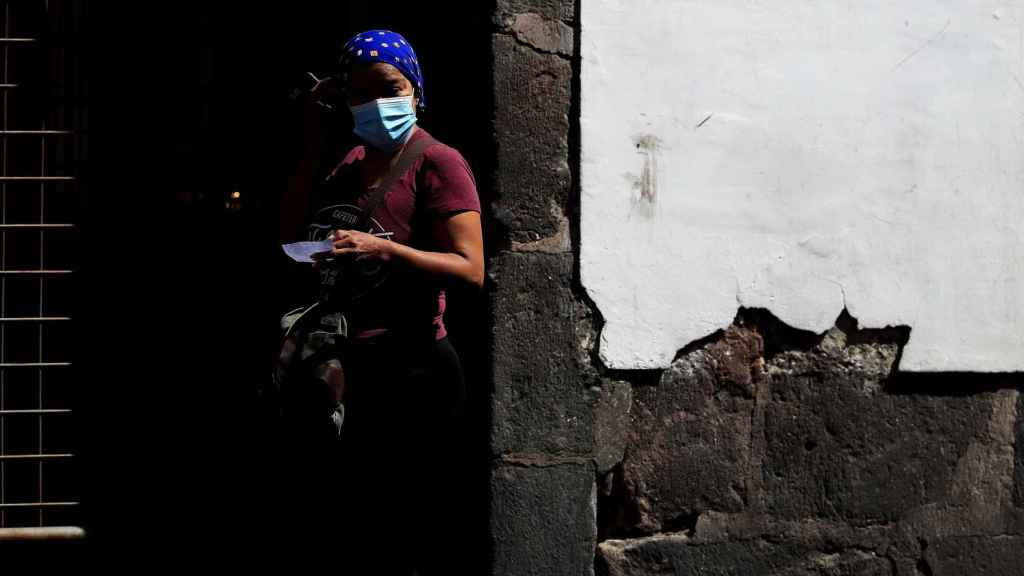na mujer con mascarilla espera en una calle hoy, en la ciudad de Quito (Ecuador).