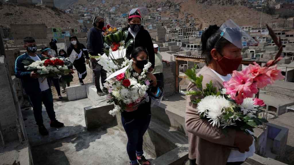 Un grupo de personas sostienen arreglos florales durante un entierro en el Cementerio del distrito de Comas.