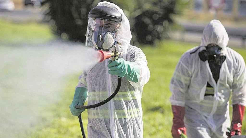 Personal fumigando para combatir el mosquito que causa el virus del Nilo.