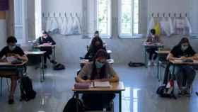 Estudiantes en su clase con mascarilla.
