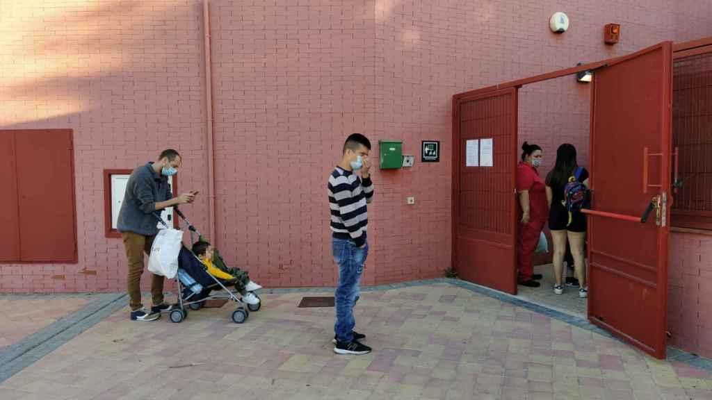 Los padres hacen cola, con distancia de seguridad, para poder acceder a la Escuela Infantil.