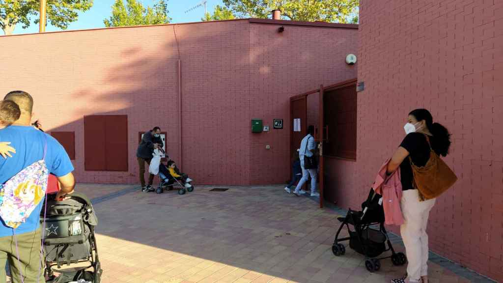 Varios padres, junto a sus hijos, esperan pacientemente a que les autoricen a acceder al centro educativo.