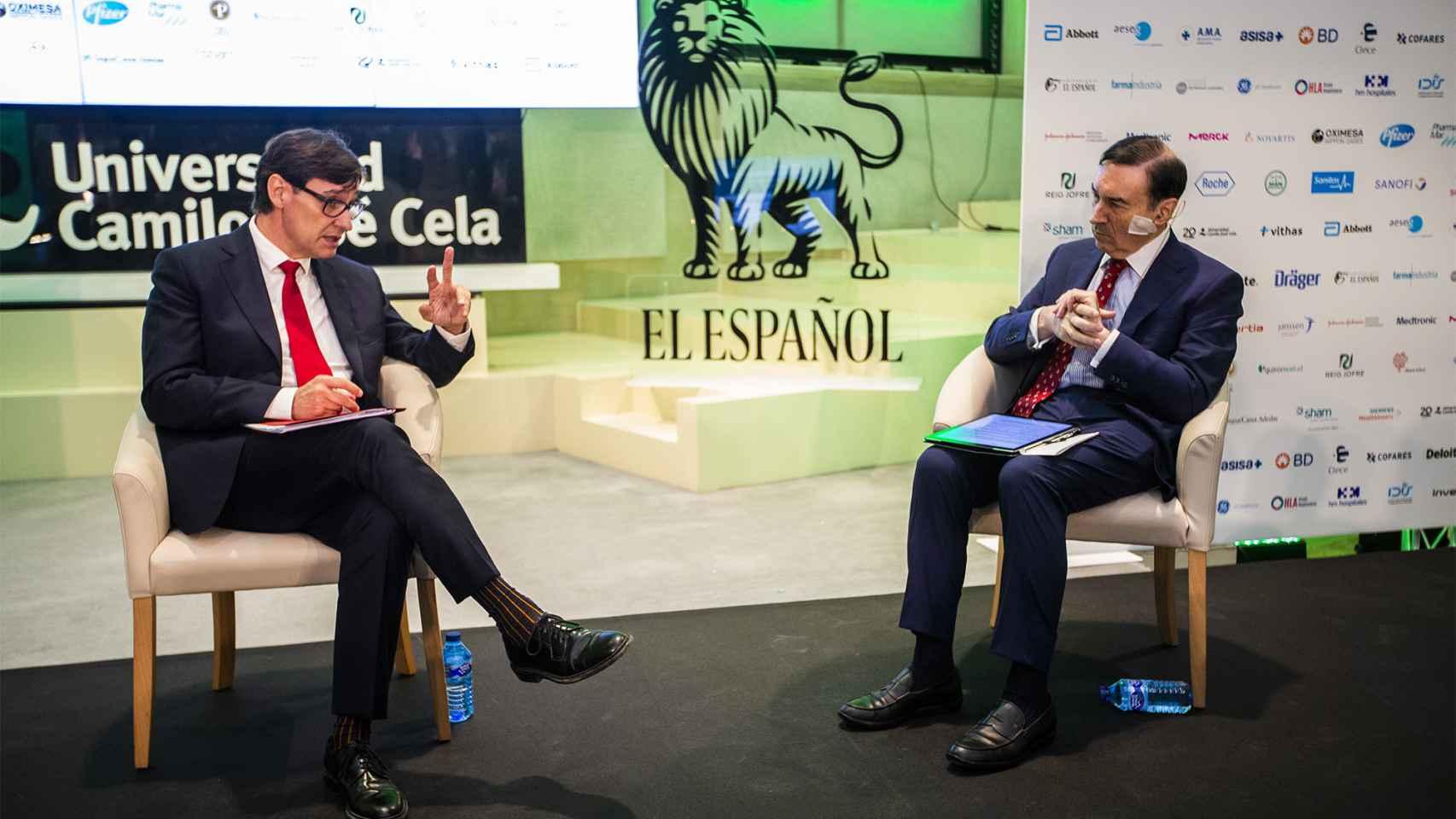 El ministro de Sanidad, Salvador Illa, conversa con el presidente ejecutivo y director de EL ESPAÑOL, Pedro J. Ramírez, durante la inauguración del simposio.
