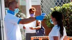 Un sanitario toma la temperatura a una joven en San Sebastián de los Reyes, Madrid. EFE/Zipi