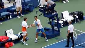Djokovic se saluda con Carreño tras ser descalificado del US Open.