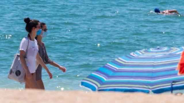Dos mujeres pasean por la playa.