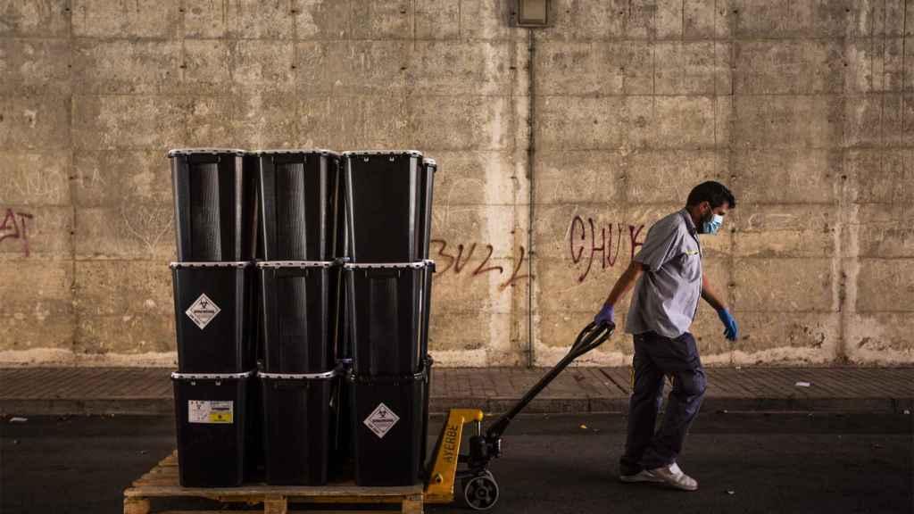 Un hombre arrastra cubos como los que se usan para desechar los EPI, en el Severo Ochoa.