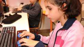 Niña ciega con ordenador en el aula