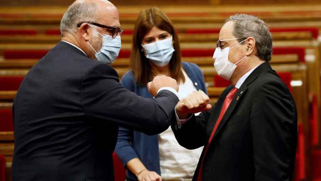 Quim Torra saluda al portavoz de JxCat, Eduard Pujol, a su llegada al Parlament.