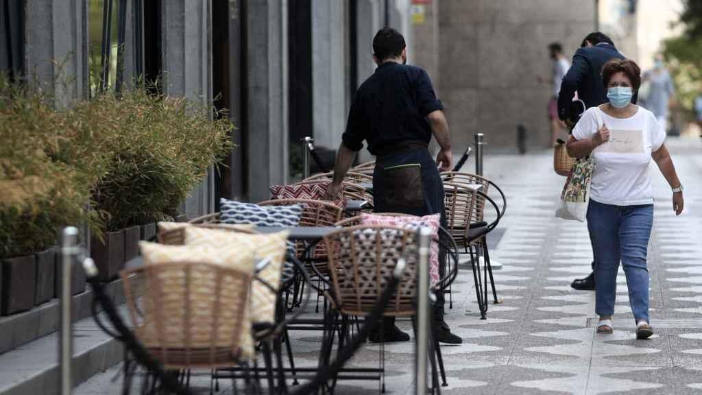 Un camarero prepara una terraza de un bar en Madrid