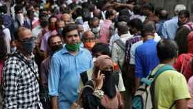 La gente guarda cola para coger un autobús en la ciudad de Bombay.