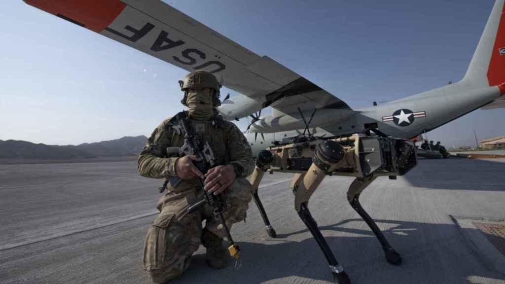 Un soldado estadounidense posa con un perro robótico