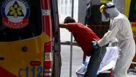 Un trabajador de Hospital 12 de Octubre equipado frente a la Covid ayuda a un paciente.