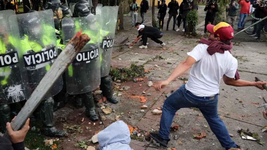 Manifestantes lanzan objetos contundentes contra los antidisturbios en Bogotá.