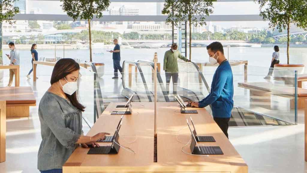 Una Apple Store con varios usuarios con mascarilla.