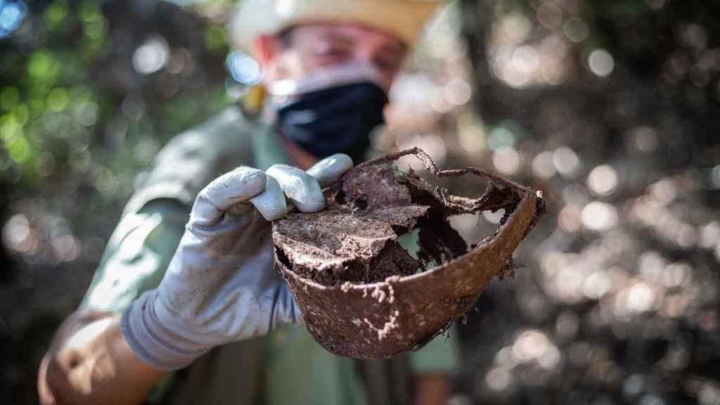 MacGyver recoge e inspecciona una pieza de hierro en el monte.