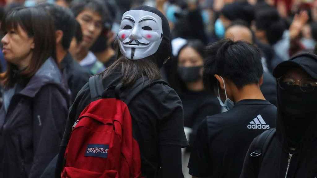 Una manifestante con máscara.