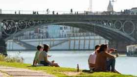 Varias personas en la orilla del Guadalquivir junto al Puente de Triana de Sevilla.
