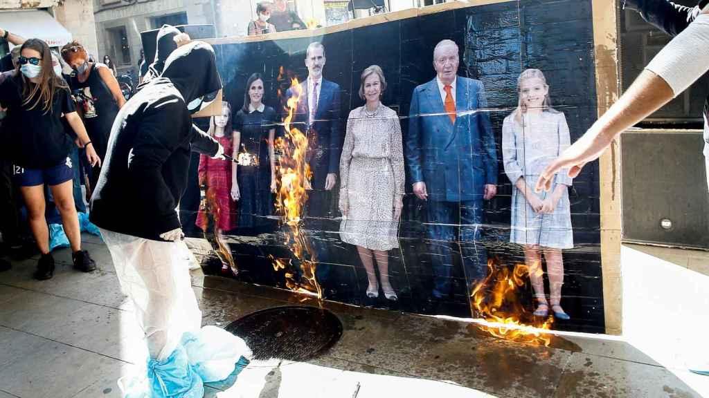 Varios jóvenes queman un retrato de la familia real durante la manifestación convocada por la organización Arran.