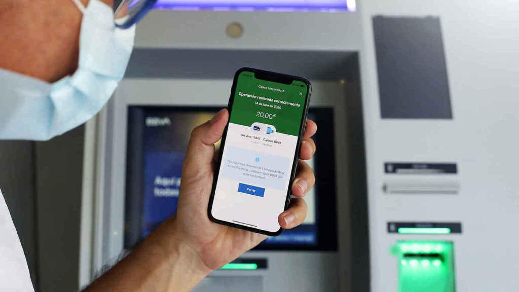 Un usuario ante un cajero automático usa una app móvil financiera.