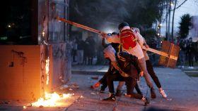 Manifestantes atacan un puesto policial en Bogotá.