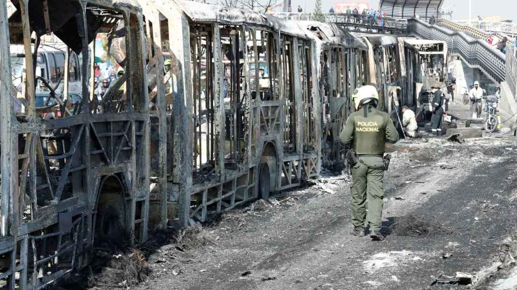 Un policía observa los restos incinerados de un autobús en la localidad de Bosa, en Bogotá.