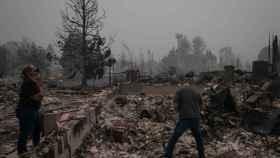 Una pareja frente a su casa arrasada por el fuego en Oregón.